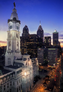 This color photograph shows City Hall circa 2005. Three of Philadelphia's tallest skyscrapers can be seen in the background, illuminated by a sunset.