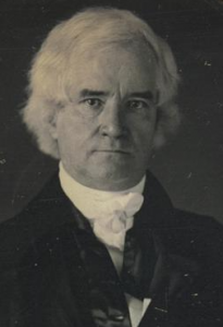 This black and white photograph shows George Mifflin Dallas. He wears a dark coat and a white shift with a ruffled collar.