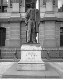 This black and white photograph shows a statue of John C. Bullitt outside City Hall. The statued figure wears a coat and vest and appears to be clutching a scroll.