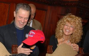 "This color photograph shows film director Jonathan Demme and Greater Philadelphia Film Office director Sharon Pinkenson at a 2008 Phillies event. Demme holds a red hat marked ""World Series Champions."""