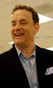 "This color photograph shows actor Tom Hanks. He is wearing a blue collared shirt and a black jacket with a label that reads ""US."""