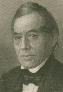 This black and white portrait depicts textile manufacturer William H. Horstmann. He wears a black suit, black bow tie and white undershirt.