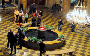 This color photograph shows the lobby of the Benjamin Franklin House. Film crew members prepare equipment and sit near the lobby's fountain.