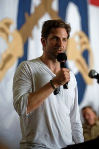 This color photograph shows Bradley Cooper answering a question at a media event.