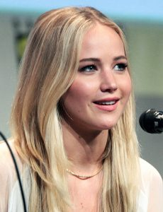 This color photograph shows Jennifer Lawrence answering a question at a media event.