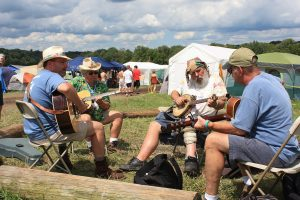 This color photograph shows four men sitting in a circle surrounded by campground tents. Three play acoustic guitars and one plays a banjo.