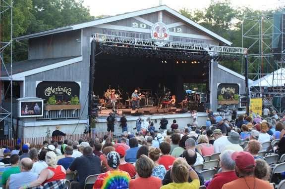 This color photograph shows a large crowd viewing a show at the Folk Festival main stage. Steve Earle, playing guitar, joins several other musicians onstage.