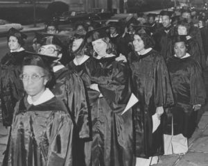 This black and white photograph shows a group of students in graduation gowns lined up on a Philadelphia street.