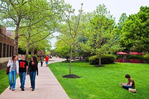 This color photograph shows the quad area of Rutgers University - Camden. Several students walk on the sidewalk or sit on the grass.