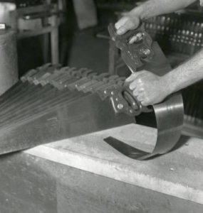 This black and white photo shows a factory worker bending a metal saw blade to ensure its sturdiness before shipment.