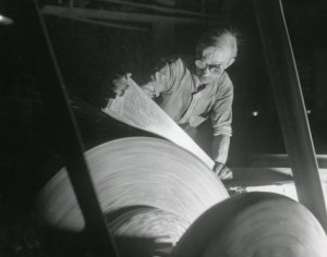 This black and white photograph shows a factory worker wearing goggles and pressing a metal saw blade against a spinning wheel to smooth out one side.