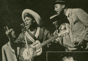 A black and white photograph of Sister Rosetta Tharpe performing in 1944. She is holding a guitar and singing into a microphone. A group of three men in suits sing behind her.