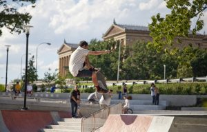 A color photograph of a man executing an aerial stunt on a skateboard using a ramp made of brick and concrete. The Philadelphia Museum of Art is visible behind him.