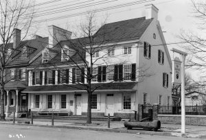 A black and white photograph of the Indian King Tavern, a white two-story building with a three-story attachment. The second floor has a row of windows with black shutters. A wooden horse trough is on the sidewalk in front.