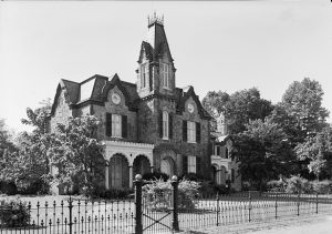 a black and white photograph of the Ebenezer Maxwell House, a gothic revival mansion with stone facade, central turret, and mansard roof. An iron fence surrounds the property.