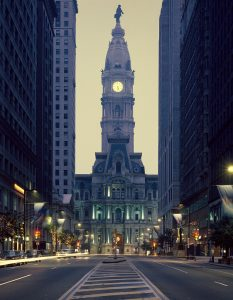 A color photograph of Philadelphia city Hall from South broad Street looking north. The building has a prominent tower with an illuminated clock face, topped with a dome and a statue of William Penn.