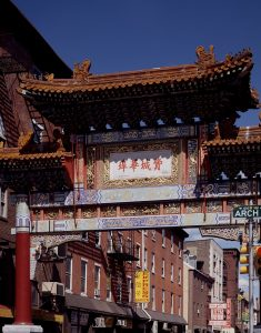 "A color photograph of the Friendship Gate, a colorful traditional Chinese gateway ornamented with golden dragons. Chinese language characters are painted in red on a white background. They translate to read the words ""Philadelphia Chinatown""."