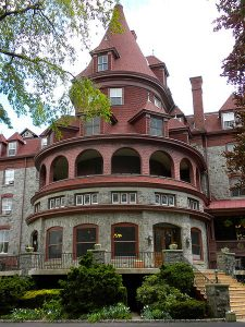 A color photo of the Bryn Mawr Hotel, a stone and red brick hotel building in the Queen Anne Style with a prominent rotunda.