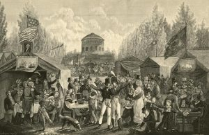 a black and white engraving of a crowd of revelers at Center Square, now Penn Square, Philadelphia in 1819. Different tents on the grounds feature musicians, games, and groups of women. Two uniformed soldiers stand arm in arm together in the front center. There are American flags and a portrait of George Washington displayed. A round pump house stands in the background surrounded by a marching band.