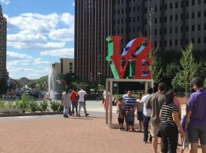 A color photograph of the LOVE Statue at John F. Kennedy Plaza, Philadelphia. A crowd waits in line for their turn to take a photo in front of the statue. There is a fountain behind it.