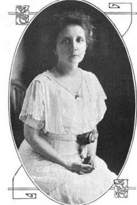 a black and white portrait of Mabel Lloyd Ridgely, seated in a white lace dress. A rolled up poster or magazine is tucked under her arm.