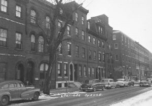 A black and white photograph of a line of three- or four-story row homes on the 600 block of Spruce Street, Philadelphia.