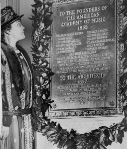 A black and white photograph of Frances Wister standing before a plaque celebrating the founders and architects of the Academy of Music. A wreath of evergreen leaves