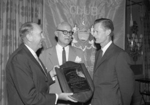 A black and white photograph of three men in suits. The two men on the left are presenting a plaque to Edmund Bacon, who stands to the right of them.