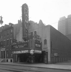 "A black and white photograph of the facade of the Boyd Theater, a 1920s-era Art Deco style movie palace. The facade is of carved white granite and an ornate entryway frames a central ticket booth. A large vertical sign on the front reads ""BOYD"" and a marquee advertises ""Theodore Dreisers Novel Jennie Gerhart"" and ""Sylvia Sidney in Jennie Gerhart"". A banner beneath the marquee reads ""Its Cool Inside!"""