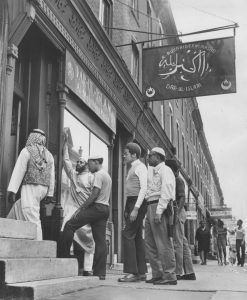 Black and white photograph depicting five muslim men in different styles of Muslim dress entering a mosque.