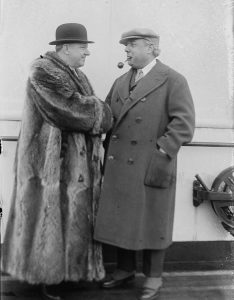 A black and white photograph of W. C. Fields, dressed in a full-length fur coat and bowler cap, shaking hands with Philip Goodman, who wears a long coat and cap and smokes a pipe. They stand on the deck of a ship.