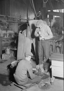 Black and white photograph depicting two men blowing glass.