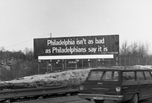 "A black and white photograph of a billboard reading 'Philadelphia isn't as bad as philadelphians say it is."" The billboard stands next to a highway. 1960s era vehicles pass by on the highway."