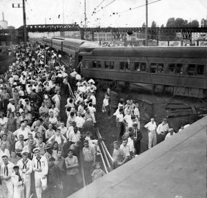Black and white photograph depicting a crowd gathering to observe a train wreck.