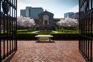 A color photograph of the main entrance of the University of Pennsylvania Museum. The photograph is taken through the iron gates and shows a formal garden with hedge rows and a reflecting pond with a stone bench in the foreground. Cherry trees in bloom flanking the front door.