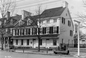 "A black and white photograph of the Indian King Tavern in Haddonfield, a white Colonial-era three-story tavern with black window shutters. A wooden horse trough stands on the street in front. a hanging sign in the foreground reads ""The Indian King""."