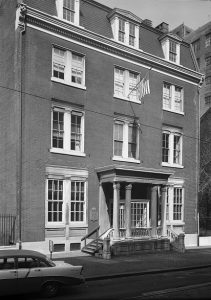 a black and white photograph of a three story brick building with a columned portico over the entrance.