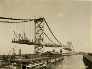 a black and white photograph of the unfinished Ben Franklin bridge taken from the Philadelphia side of the Delaware River. The cables and pillars are completed but there are large gaps in the road bed.  In the foreground are several marinas and piers on the river. In the background is the skyline of the city of Camden.