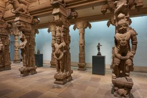 life-sized figures of Indian deities carved into stone pillars with ornate decorations.