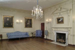 Interior of eighteenth-century parlor room with portraits on the walls, blue furniture, a fireplace, and a crystal chandelier.