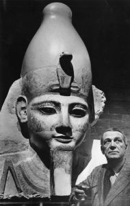 A black and white photograph of Froelich G. Rainey standing in front of a colossal ancient bust of Ramses the second of Egypt. The statue wears a crown adorned with a rearing cobra.