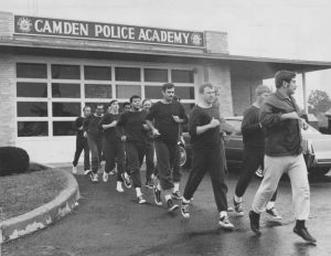 A black and white photograph of a line of men jogging on pavement in front of the Camden Police Academy. All of the men wear identical sweat suits except the instructor