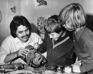 A black and white photograph of a man holding a mask, which a young boy is painting. Another young boy stands nearby and watches.