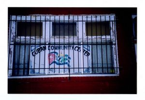 "A color photograph depicting a sign with a Cuban flag and the text ""Cuban Community Center."""