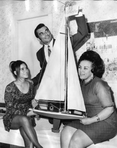 Black and white photograph showing two seated women holding a model boat. A Man stands behind them.