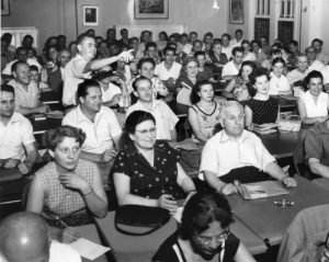 Black and white photograph showing adult students sitting at desks. Instructor is pointing at something in the front of the room.