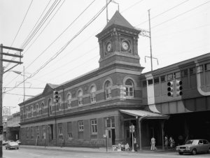 A black and white photograph of the wilmington train station showing a three story clock tower, covered railway on the second story, and entrances on the ground floor.