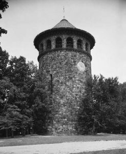 A black and white photograph of Rockford tower, a tall cylindrical stone tower with a pyramidal roof. The upper floors are lined with arched windows. There is a sundial embedded in the stone below the windows. The tower stands in a park surrounded on two sides by trees, with a walking path leading towards it.