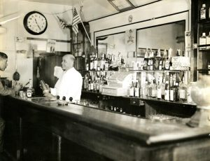 Black and white photograph depicting a man behind a bar preparing a drink while talking to a seated man.
