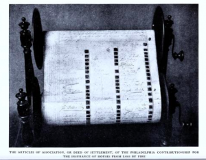 a black and whit photograph of a scroll of paper held on two wooden reels with cranks. The scroll has a list of signatures on it.